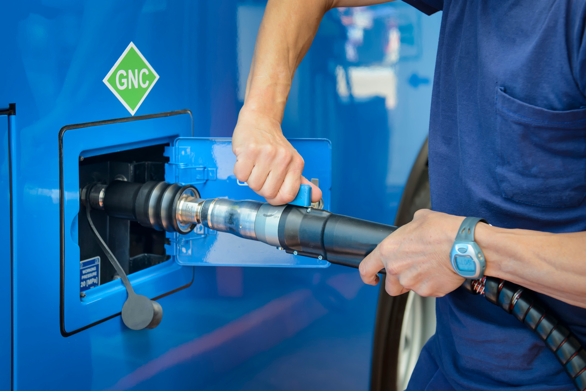Personne rechargeant un véhicule roulant au gaz naturel