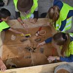 Des archéologues et des enfants font des fouilles au musée archéologique Lattara