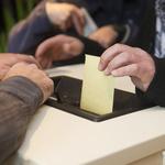 Gros plan sur une main qui glisse une enveloppe dans une urne